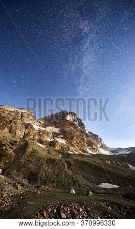 Camp Tents In Hillside Valley With Mountains Under Blue Sky With Stars. Scenery Of Milky Way Over Mo