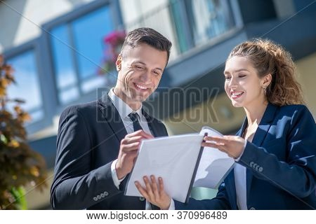 Well-dressed Male Client Signing The Documents, Female Broker Looking Pleased