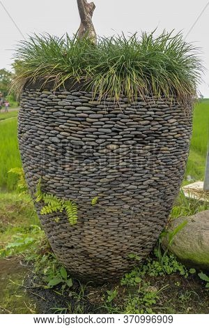 Huge Flower Pot Made Of Small Black Pebbles. Ornamental Flower Pot Placed In Nature. Ornamental Gras