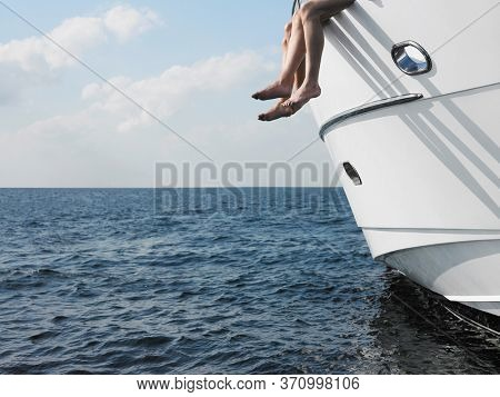 Low angle view of couple's legs with bare feet dangling over the side of a yacht