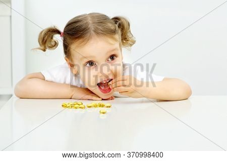 The Child Is Happy To Try Omega 3 Fish Oil, In A Bright Room, Yellow Capsules, White Table, White Ba