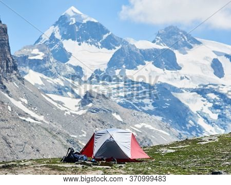 View Of Mountain Valley With Tourist Tent And Hiker Belongings. Picturesque Scenery Of Camp Tent Wit