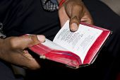 Two hands holding an old well-used prayer book at a Methodist church service on Sunday are symbolic of faith of South African people. Note: shallow depth of field is focused on just the thumb and the nearby text. poster