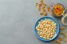 Dried Pumpkin Slices And Seeds On A Gray Stone Background. Candied Pumpkin. Top View With Copy Space