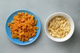 Dried Pumpkin Slices And Seeds In Bowls On A Gray Stone Background. Candied Pumpkin. Top View.