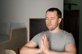 Young Adult Man Stands In A Tree Pose While Doing Yoga At Home. Mental Health. Home Interior, Daylig