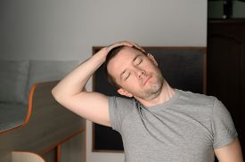 Young Adult Man Doing Stretching During A Workout At Home. Mental Health. Home Interior, Daylight.