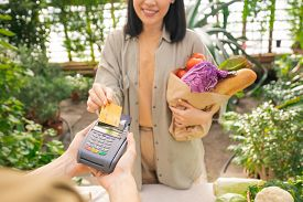 Close-up of smiling lady holding paper bag full of vegetables and paying for organic food with credit card in grocery store