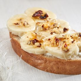 Sandwich With Banana Slices Sprinkled With Nuts Close Up On A White Wooden Table.