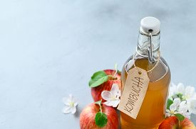 Homemade Fermented Kombucha Drink In A Glass Bottle And Fresh Apples On A Light Gray Stone Table. A