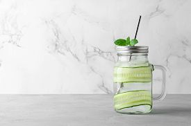 Refreshing Cocktail With Cucumber Slices, Mint Leaves And Ice Cubes In Jar. Light Gray Concrete Tabl