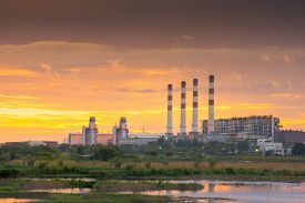 Production Line In Thermal Power Plant And Power Lines During Sunset