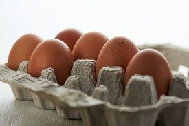 Eggs In A Protective Container On White Background. Foreground And Background In Blur.