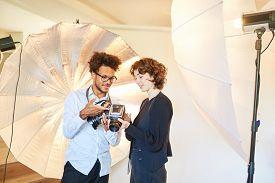 Photo students look on retro medium format camera in the photo studio
