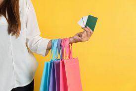 Woman With Shopping Bags And Bank Or Credit Card In Mall On Yellow Background