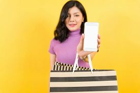 Woman Hand Shopping Using Smartphone With Shopping Bag On Yellow Background