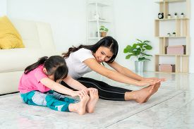 Asian Mother And Daughter Doing Fitness Exercises In Living Room At Home To Maintain Physical And Me