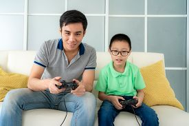 Asian Family Father And His Son To Playing Video Games With Joysticks While Sitting In Sofa In Livin