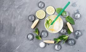 Mojito Drink On Grey Background. Lime, Lemon, Mint Leaves And High Glass With Ice Cubes. Summer Low