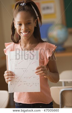 Young girl showing test score of 100