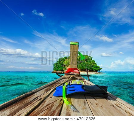 Vacation holidays adventure  concept background - tropical island and long-tail boat  with snorkeling set. Thailand
