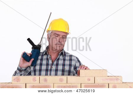 A mason with a drill.