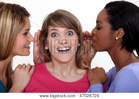 Two women whispering into friends ear