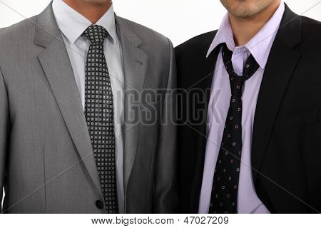 One executive with a perfect tie, another with a loosened tie