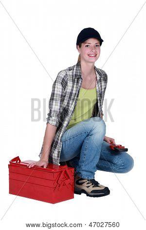 Woman kneeling by tool kit