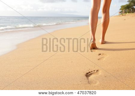 Beach travel - woman walking on sand beach leaving footprints in the sand. Closeup detail of female feet and golden sand on Kaanapali beach, Maui, Hawaii, USA.