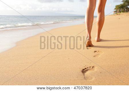 Playa viajar - mujer que camina en dejando huellas en la arena de la playa de arena. Detalle de primer plano de mujer
