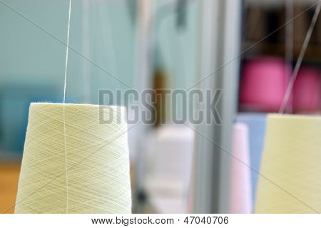 Image of yellow spools and thread background