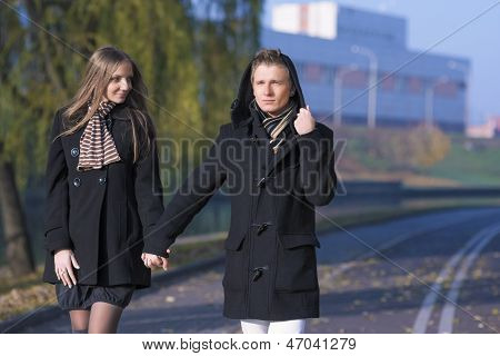 Portrait Of Young Caucasian Couple Walking Together Outdoor With Hands Connected