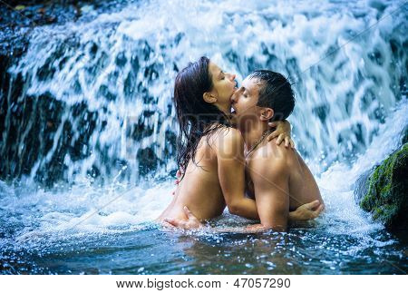 Couple hugging and kissing under waterfall