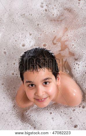 Happy child bathing in bathtub