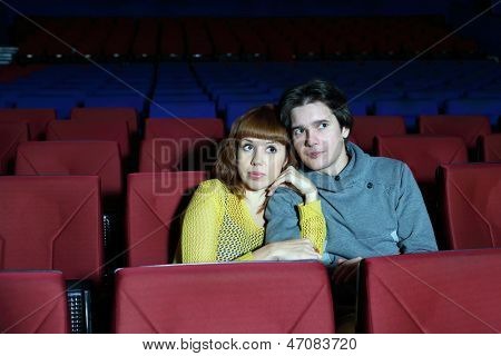 Young man and woman watch movie, embrace and fear in cinema theater.