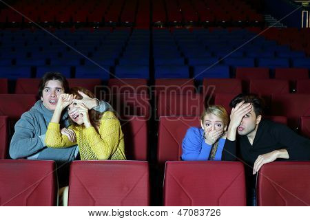 Four young scared friends see movie in cinema theater and blind eyes by hands.