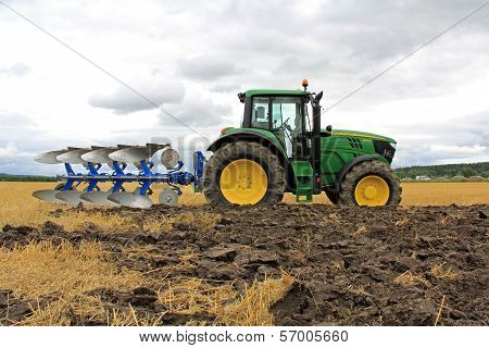 John Deere 6150M Tractor With A Plow On A Field