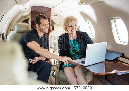 Businessman with female colleague discussing over laptop on private jet