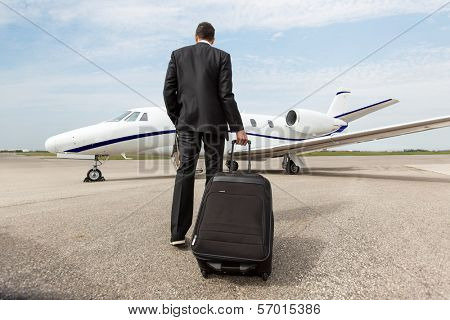 Rear view of businessman with luggage walking towards corporate jet