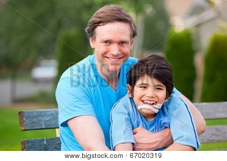 Handsome Father Holding Smiling Disabled Son Outdoors
