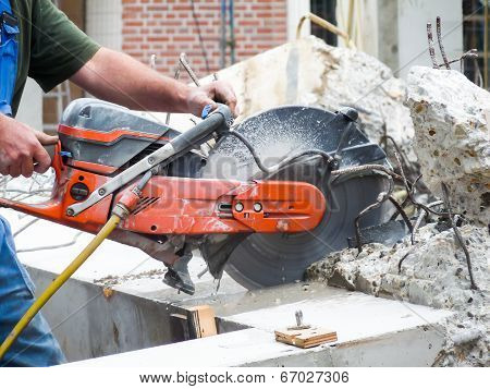 Arms holding grinder cutting concrete