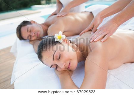 Attractive couple enjoying couples massage poolside outside at the spa