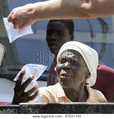 SAINT MARC, HAITI - FEBRUARY 22, 2013:  Close-up of an elderly Haitian woman accepting a bags of drinking water distributed from the back of a mission truck.