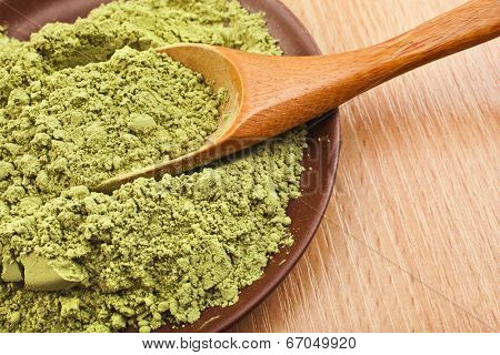 Powdered Green Tea Matcha in spoon on wood table surface close up