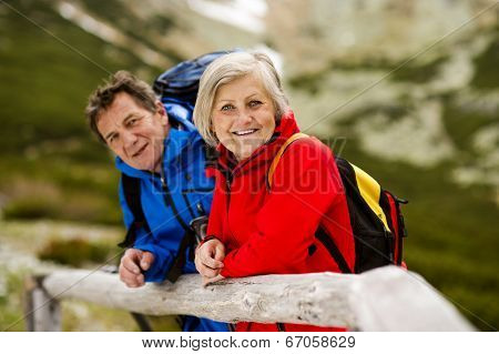 Senior tourist couple hiking at the beautiful mountains poster