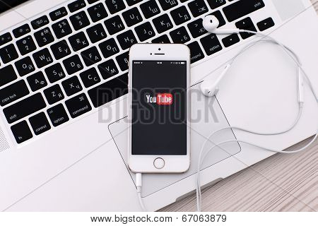 White Iphone 5S With Site Youtube On The Screen And Headphones Lies On The Keyboard Macbook