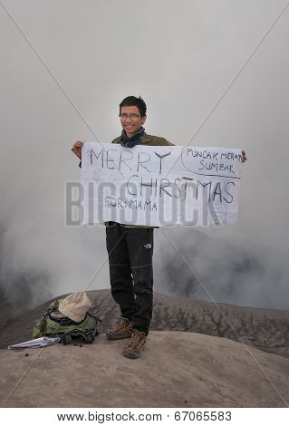 Unidentified Indonesian Student With Poster For Parents On The Top Of Volcano Merapi