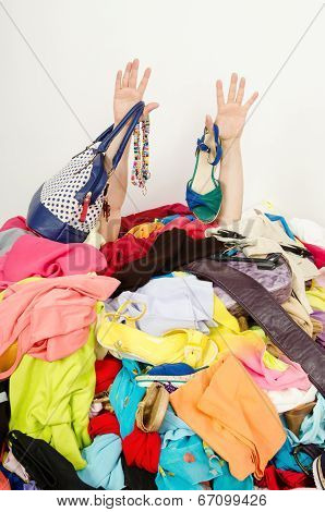 Man buried under an untidy cluttered woman wardrobe. Man reaching for help from to much woman shopping. poster