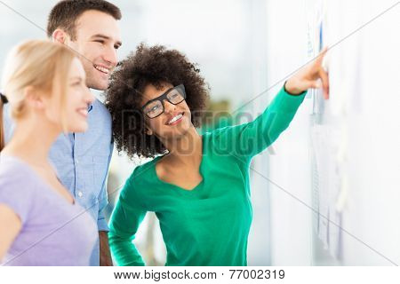 Young business people discussing on adhesive notes